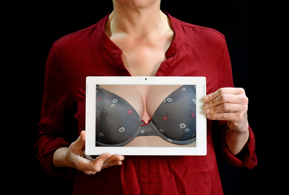 girl with a tablet on hands showing breasts